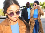 Selena Gomez might battle with her weight but she's  looking good showing midriff in high waisted jeans catching a flight at LAX signing autographs for fans. November 24, 2015 X17online.com