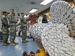 U.S Army soldiers serving in the NATO-led peacekeeping mission in Kosovo wait in line to be served a traditional Thanksgiving meal by their superiors in a U.S. military base Camp Bondsteel, near the village of Sojeve in Kosovo on Thursday, Nov. 26, 2015. It is the 16th Thanksgiving for hundreds of U.S. solders serving in the NATO-led peacekeeping mission in Kosovo. (AP Photo/Visar Kryeziu)