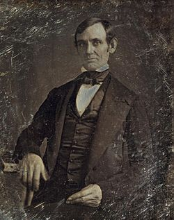 Middle aged clean shaven Lincoln from the hips up.