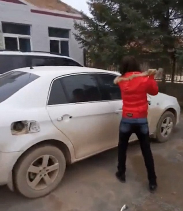 Revenge: The furious woman delivered dozens of blows to the doomed car, after finding out her husband was cheating on her