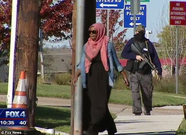 Threatening: The group said they wanted to show force by carrying guns. Worshippers tried to avoid the rally as they made their way in to prayer services on Saturday. Here, a protester is seen following a worshipper