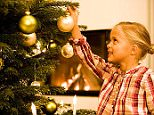 A stock photo of a young girl decorating christmas tree.