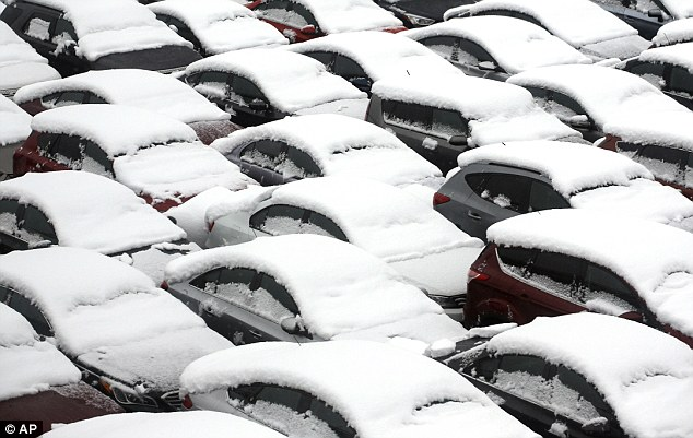 Cars are covered by snow in a rental car parking lot at Chicago's O'Hare International Airport seen Saturday