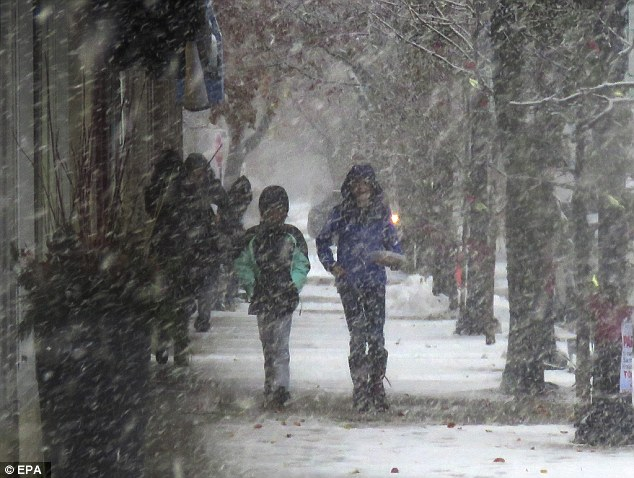 People walked down a snowy sidewalk  in Wilmette, Illinois, as temperatures across the state began to plunge