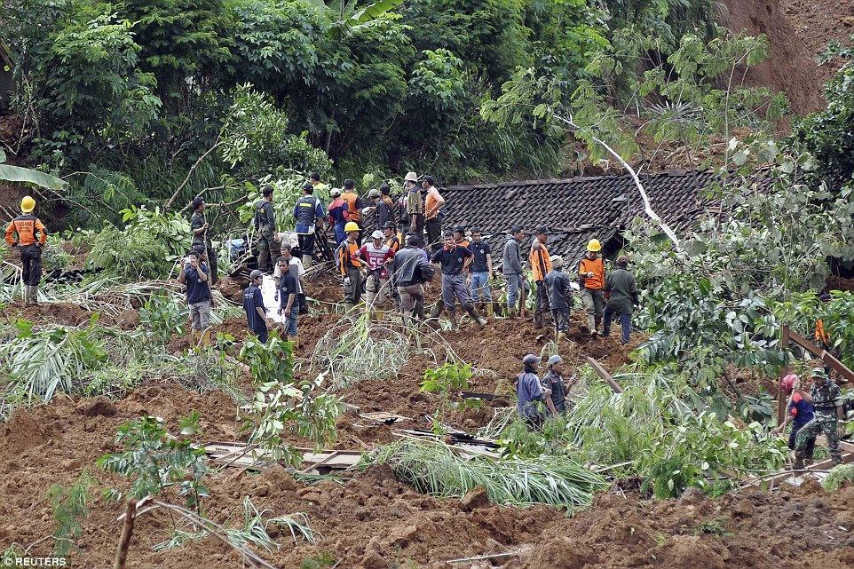 Rescue workers stand near houses buried in the mud after a landslide hit the village of Jemblung in Banjarnegara. A 'rain' of red soil covered 100 homes on Friday night. Rescuers are still searching the debris