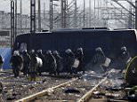 Greek riot police officers deploy at Idomeni railway station in northern Greece by the border with Macedonia, photographed from the Macedonian side of the border, near town of Gevgelija, on Wednesday, Dec. 9, 2015. Greek riot police have removed hundreds of protesting migrants from a border crossing to Macedonia, which is denying them entry, deeming them to be economic migrants and not refugees. Macedonia, along with Serbia, Croatia and Slovenia, is turning away from its borders migrants who are not from war zones such as Syria, Afghanistan and Iraq. (AP Photo/Boris Grdanoski)