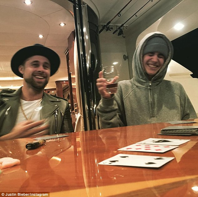 Boys' night: Meanwhile Justin was also hanging out with his pals, over some drinks and card games