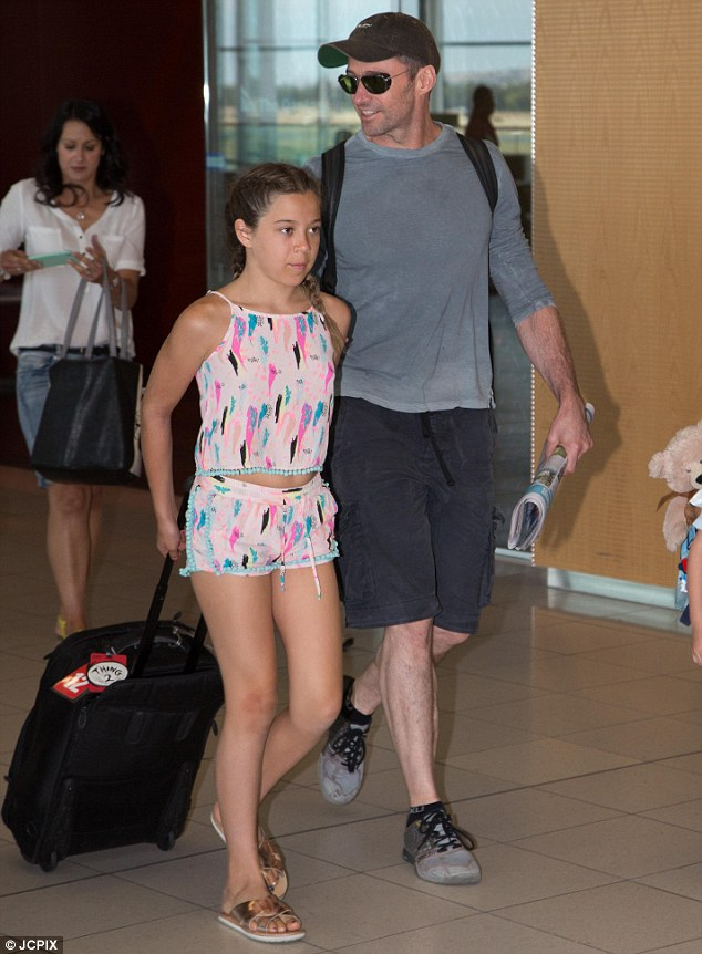 Cute: His daughter looked cute in a matching singlet and shorts set with gold sandals as she walked closely with her father