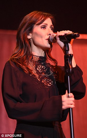 Fashionable singer:The stylish number was teamed with a matching black blouse, the long-sleeved top embellished with lace detail across the high neckline