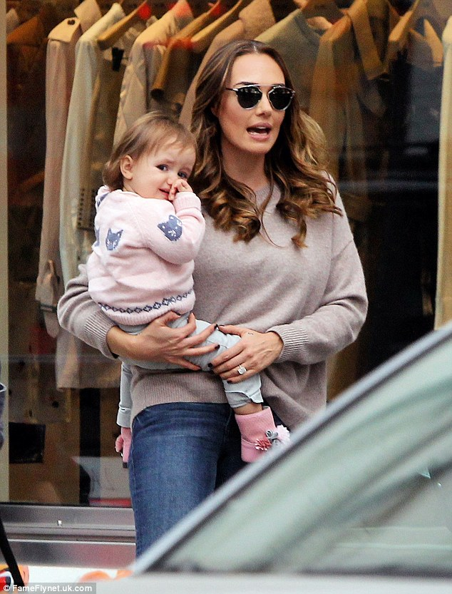 Cuddles: The happy family were spotted Christmas shopping in New York City at the weekend, in what is their 13th holiday of the year