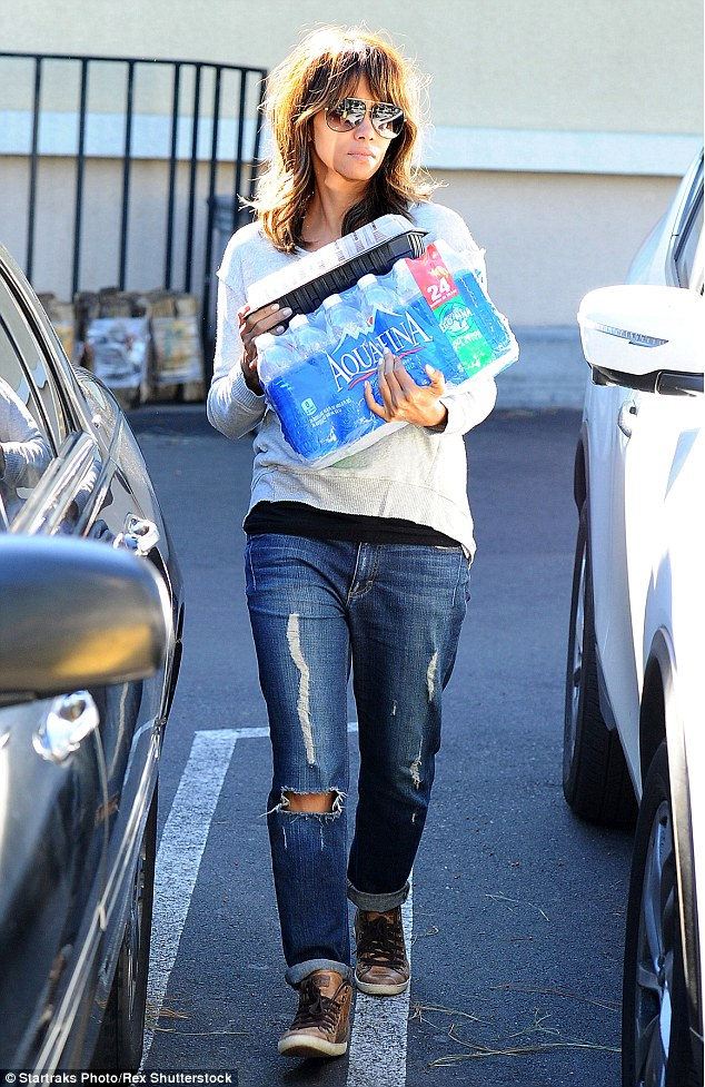 Quenching her thirst! Halle Berry, 49, looked youthful as she went makeup-free while stocking up on a large case of bottled water in Los Angeles on Saturday