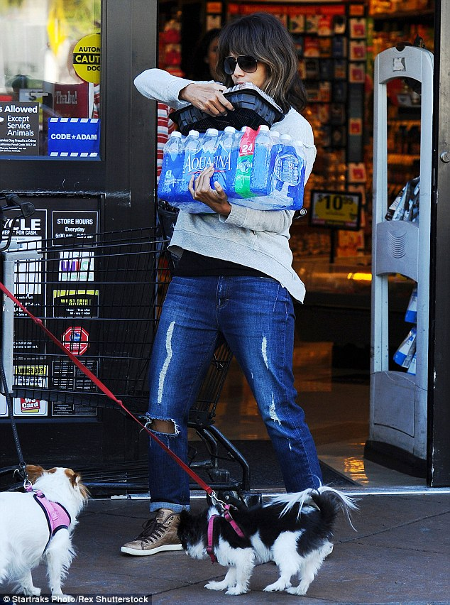 Heavy lifting! The Oscar winner had her hands full as shecarried the package of Aquafina to her car along with some deli produce