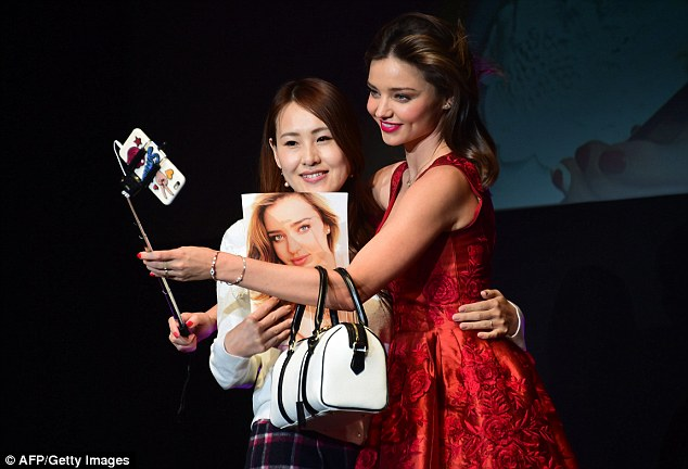 Lucky lady: One fan was called up on stage to take a snap with the model