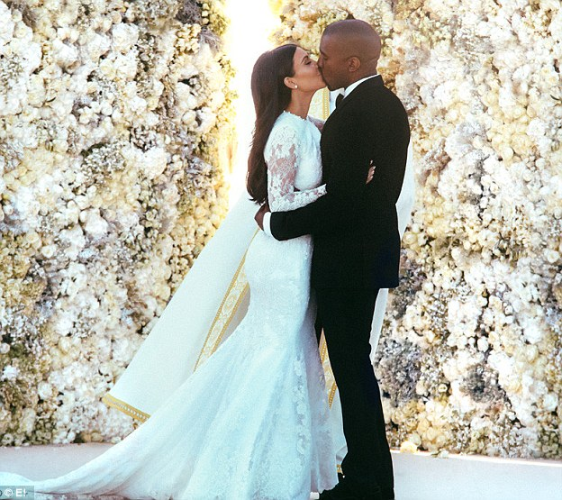 Over-the-top: Kim Kardashian and Kanye West kiss in front of a wall of flowers at their 2013 wedding