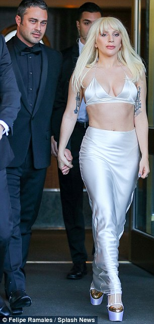 Power couple: The Applause singer stunned in the light hued ensemble, wearing a silky maxi skirt and cleavage-revealing bralette while Taylor looked dapper in an all-black suit