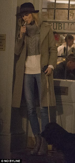 Donna dressed in a pair of stone-washed jeans, a smart dark cream-coloured coat and chic fedora hat