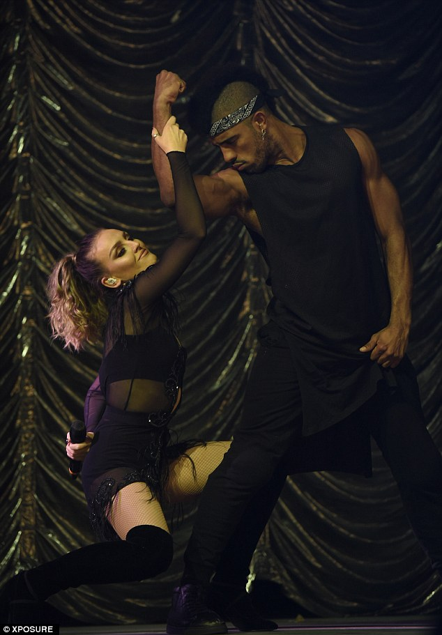 Having fun: At one point, she smiled to herself as she held onto the sexy backing dancer