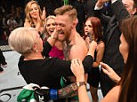 Conor McGregor hugs his mother as his family and friends surround him following his UFC 194 victory