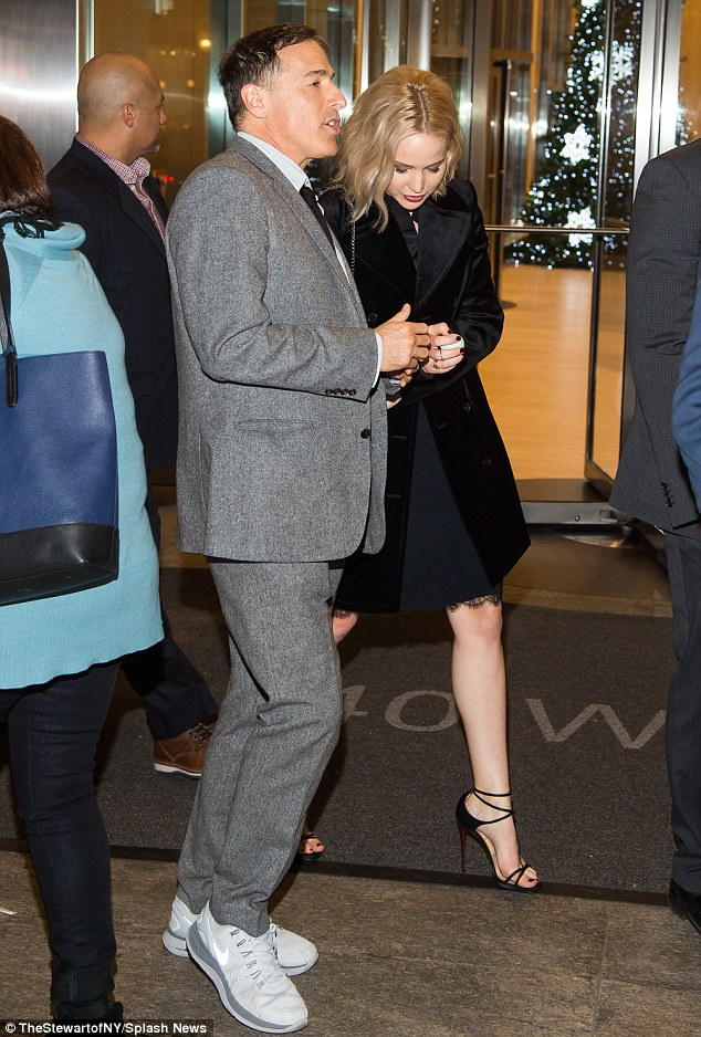 Dressed in layers: Jennifer sported a little black dress with lacy elements that ended just above the knee, though she kept it mostly hidden with a wide-collared black velvet trenchcoat