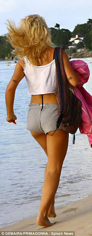 Skimpy beach attire: Jess flashed her flat stomach in a white jersey crop-top and rolled up her thigh-grazing shorts so that her petite pins could be seen