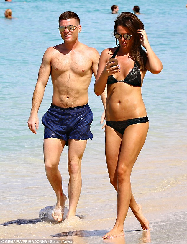 Selfie queen: Danielle was seen avidly checking her phone as she joined Michael on a stroll down the beach
