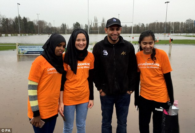Khan poses for a photo with three girls as he stands on the ground of a flooded rugby club