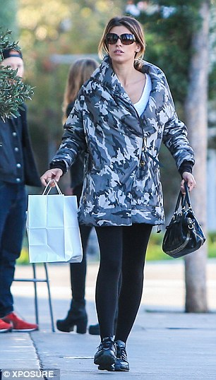 Unflattering: The star, who famously dated George Clooney for two years, bundled up her small frame in an oversized camouflage coat, but highlighted her toned pins in a pair of tight black leggings