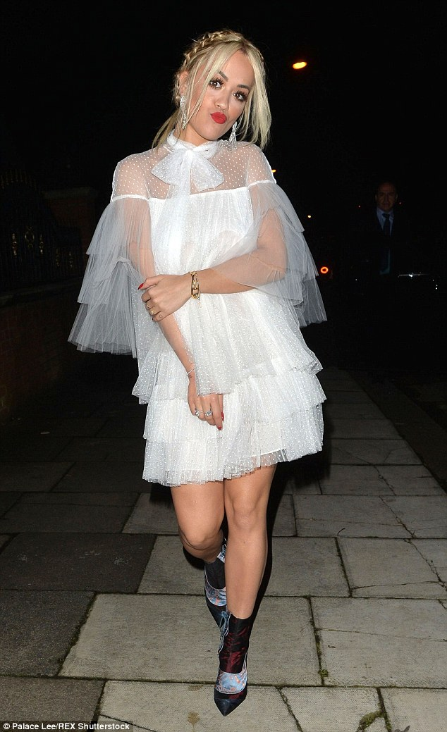 Kiss, kiss:Trading her dramatic and glamorous ball gowns for a layered white mini dress, the 25-year-old pop star donned a flirty white dress laden with frills