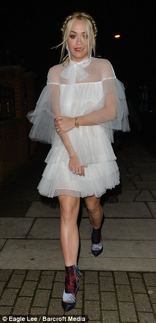 Pretty and prim:Despite carrying off the flirty look with aplomb, Rita appeared to be feeling the brusque December chill as she draped her arms around her body to brace against the weather