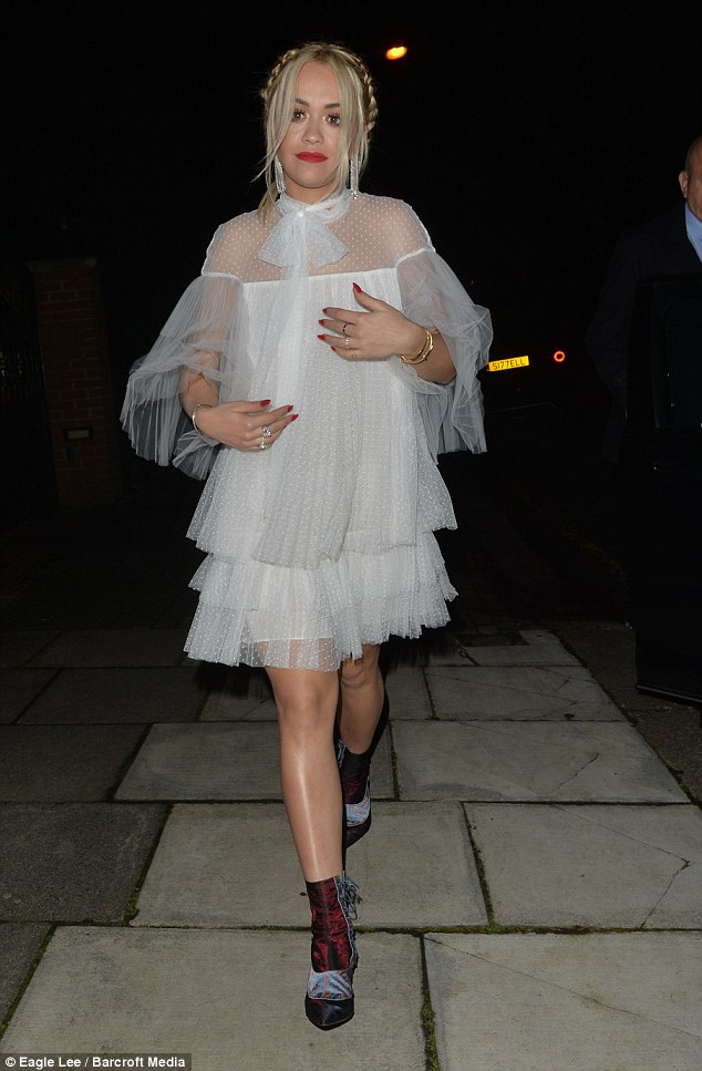 Unusually demure:Slipping into the frilled mini dress, which featured a Victoriana-style pussybow neckline and oversized sleeves, she drowned her sensational figure in the name of fashion