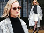 """12/13/2015\nJennifer Lawrence exits the Greenwich Hotel on the way to a press junket for """"Joy"""" in New York City. Ms Lawrence stepped out looking fab in long white and gray knit coat, and black turtleneck and white fringe skirt. \nsales@theimagedirect.com Please byline:TheImageDirect.com"""