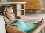 A stock photo of a woman laying on sofa and texting with cell phone.   Image shot 2013. Exact date unknown.