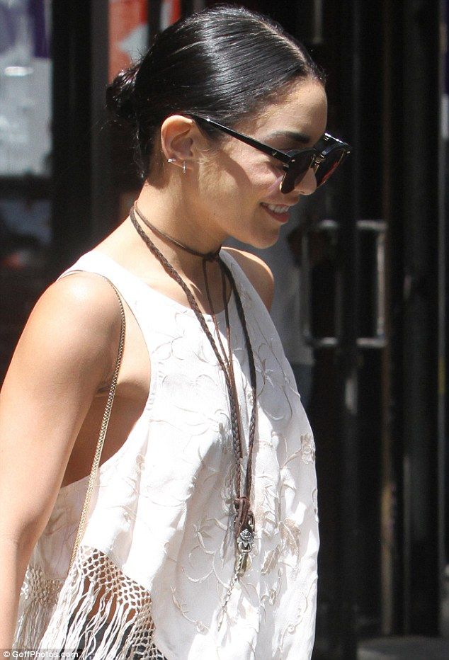 Finishing touches: She accessorized with a chic white purse with a chain strap and a pendant necklace while concealing her eyes behind dark oversized shades