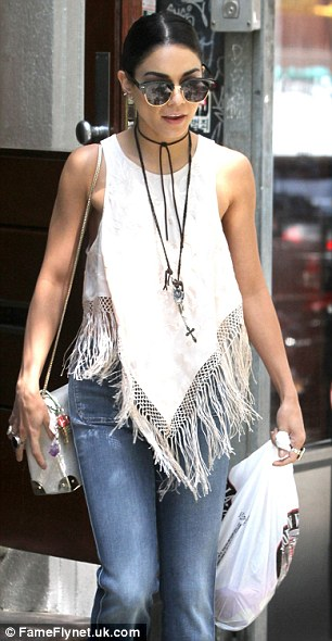 Boho babe: The 26-year-old actresshighlighted her slender frame in bell bottom jeans paired with a white fringe top featuring an asymmetrical hemline and a floral design