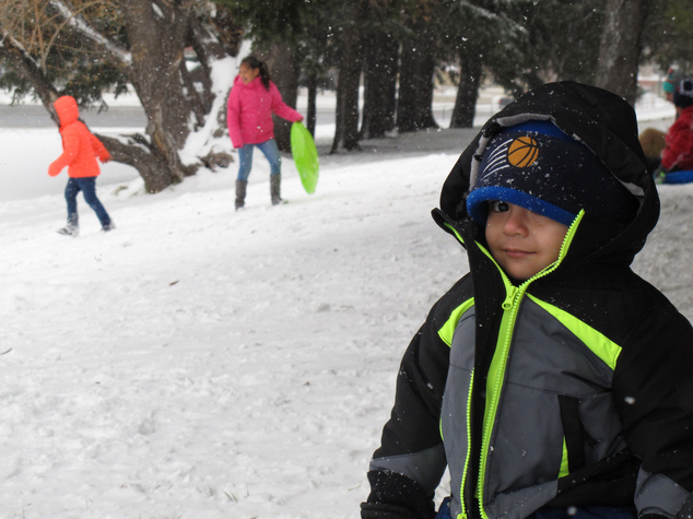 Angel Cisneros, 2, of Phoenix, watches family members sled down a hill on Monday, Dec. 14, 2015 in Flagstaff, Ariz. Wintry weather had traffic crawling along...