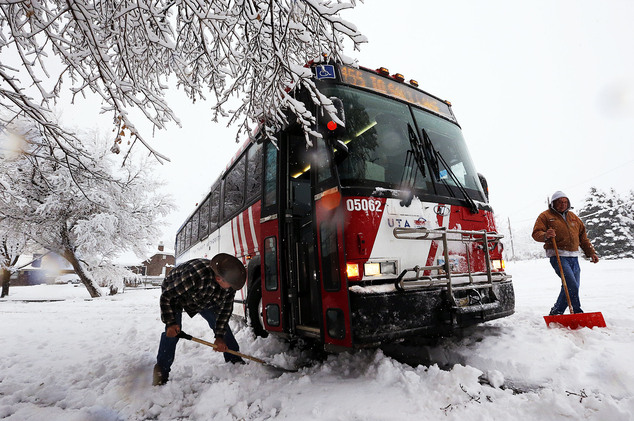 Good Samaritans Kim Brown, left, and Kerry Munk work to help free a bus stuck in the snow in Farmington, Utah, Monday, Dec. 14, 2015. Cities along the Wasatc...