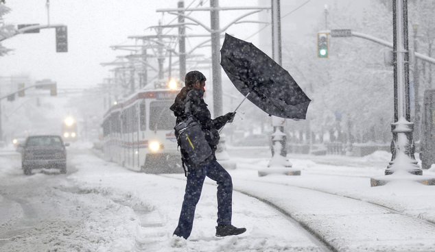 A man's umbrella blows inside out as he walks along downtown Salt Lake City Monday, Dec. 14, 2015. The first major winter storm of the season dumped up to a ...