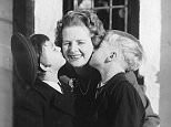 Margaret Thatcher, centre, being kissed by children Carol, left, and Mark, before they left for school