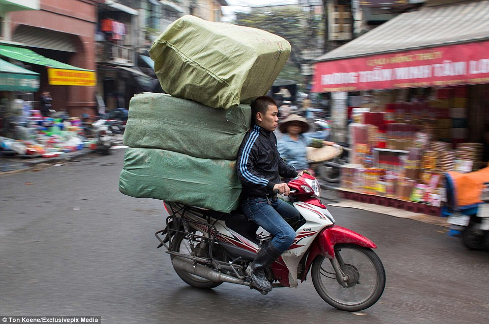 This rider appears to be in an uncomfortable position while transporting giant sacks filled with goods