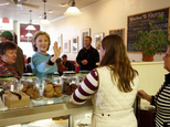 FILE - In this April 20, 2015, file photo, Democratic presidential candidate Hillary Clinton waves to employees at Kristin's Bakery during her first New Hampshire campaign stop in Keene, N.H. Clinton knows from three previous trips down the presidential campaign trail, politicking means picking your food carefully. Since launching her campaign bid in April, Clinton has embarked on a rigorous diet plan, hoping to stave off the pounds that often accompany the near-sleepless nights and non-stop snacking of a campaign. (AP Photo/Jim Cole, File)