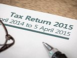 F0TJNJ UK HMRC Income tax return form for 2015 on a desk with pen and glasses