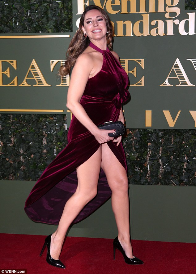 She's a LEG-end! Clearly proud of her buxom and curvaceous figure, she smiled as she greeted onlookers in the maroon-coloured design