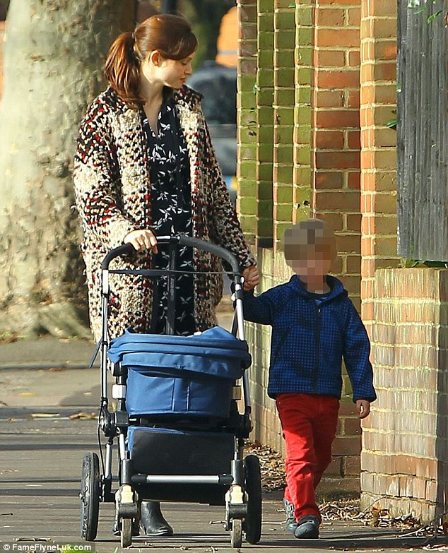Multi-tasking: As she pushed Jesse in the pram, the star also kept a firm grip on her three-year-old son's hand
