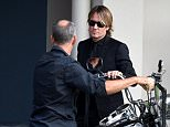 """Australian country singer-songwriter Keith Urban (right) and his brother Shane wheel their father's Robert """"Bob"""" Urban's Harley Davidson during his funeral service in Caloundra on the Sunshine Coast, Thursday, Dec. 17, 2015. Robert Urban is the father of country singer-songwriter Keith Urban. (AAP Image/Dan Peled) NO ARCHIVING"""