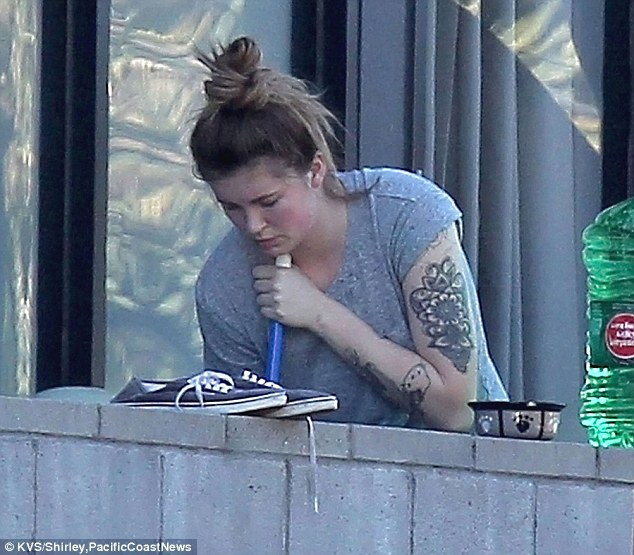 Hard at work: The star could be seen sweeping out on her balcony in Los Angeles before meeting up with her mother