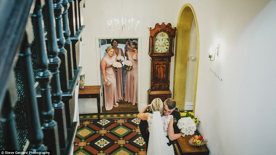 This photo shows the emotions of a father giving his daughter away - here, bride Lyndsey Gibbons is greeted at the bottom of the stairs by her dad in military uniform before they head to church together