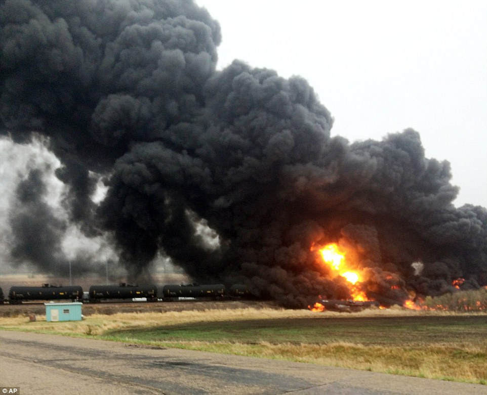 Raging fire: This photo provided by Curt Bemson shows smoke and fire coming from an oil train that derailed Wednesday, May 6, in Heimdal, North Dakota. Officials said ten tanker cars caught on fire on theBurlington Northern-Sante Fe Railway