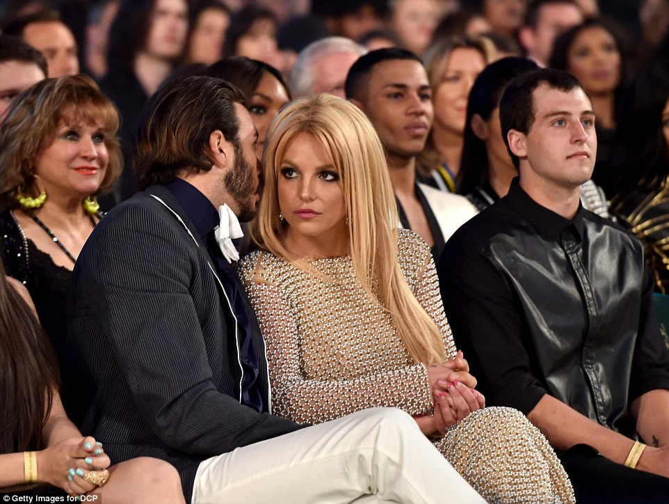 Looking fine: Britney wore an almost sheer dress as she sat next to Charlie Ebersol
