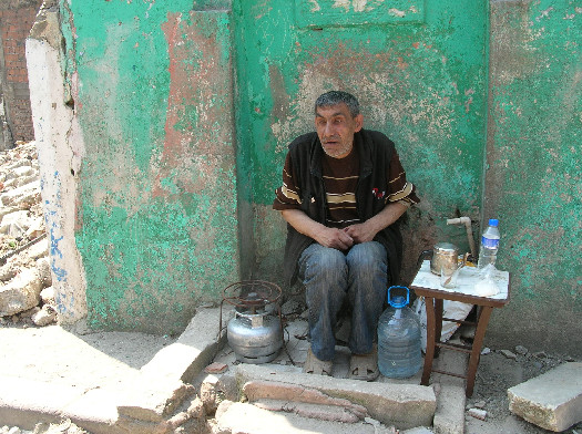 This man has a portable stove, drinking water, and a coffee pot. But he needs more than a wall to maintain his community. (Photo: Hacer Foggo)