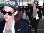 Kristen Stewart looking like a tomboy but wearing a fitted tuxedo jacket and carrying a Chanel bag arriving alone for a flight at LAX. Wednesday, January 13, 2016. X17online.com